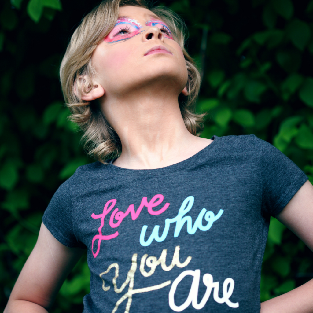 a child with a shirt that says 'love who you are' looking proud