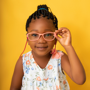 a child with glasses looking at the camera